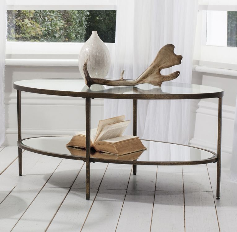 Amazing Design Of The Oval Glass Coffe Table With Black Iron Legs Added  With Some Sculpture