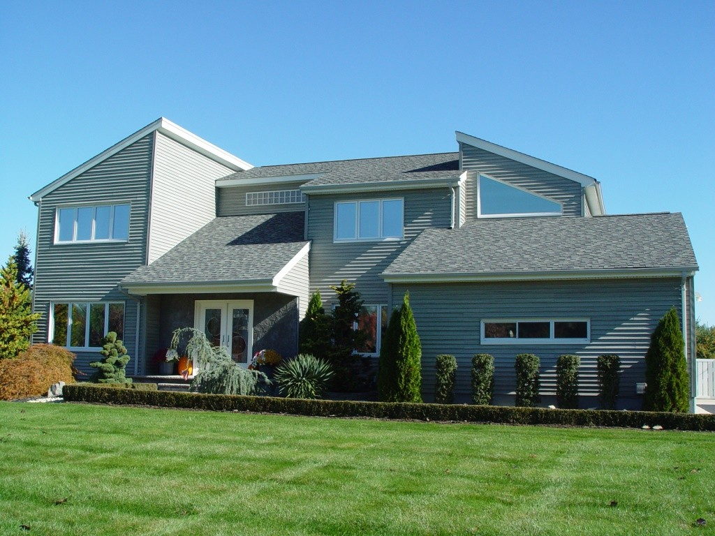 Awesome Design Of The Modern Style Homes With Blue Wall Added With Wide Open Grass Areas And Some Trees