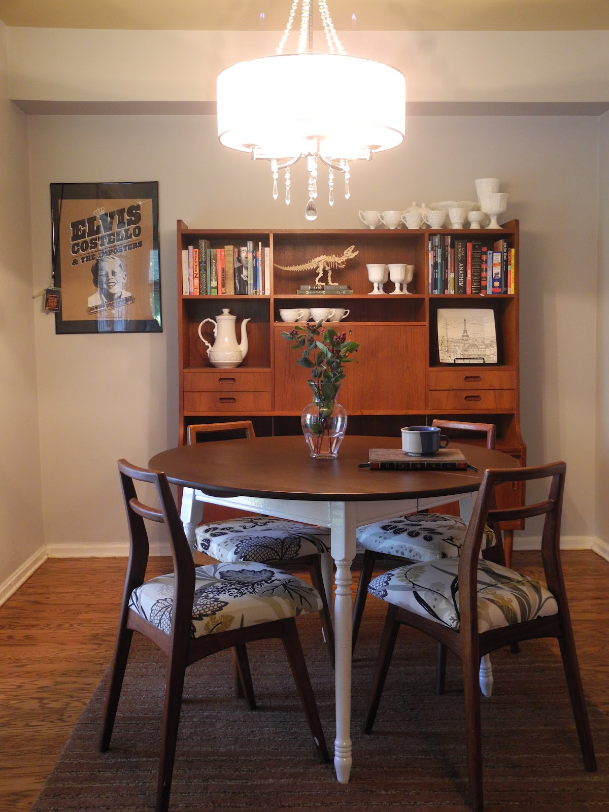 Delightful Chandelier Above Minimalist Round Table and Chair Beside Bookshelve
