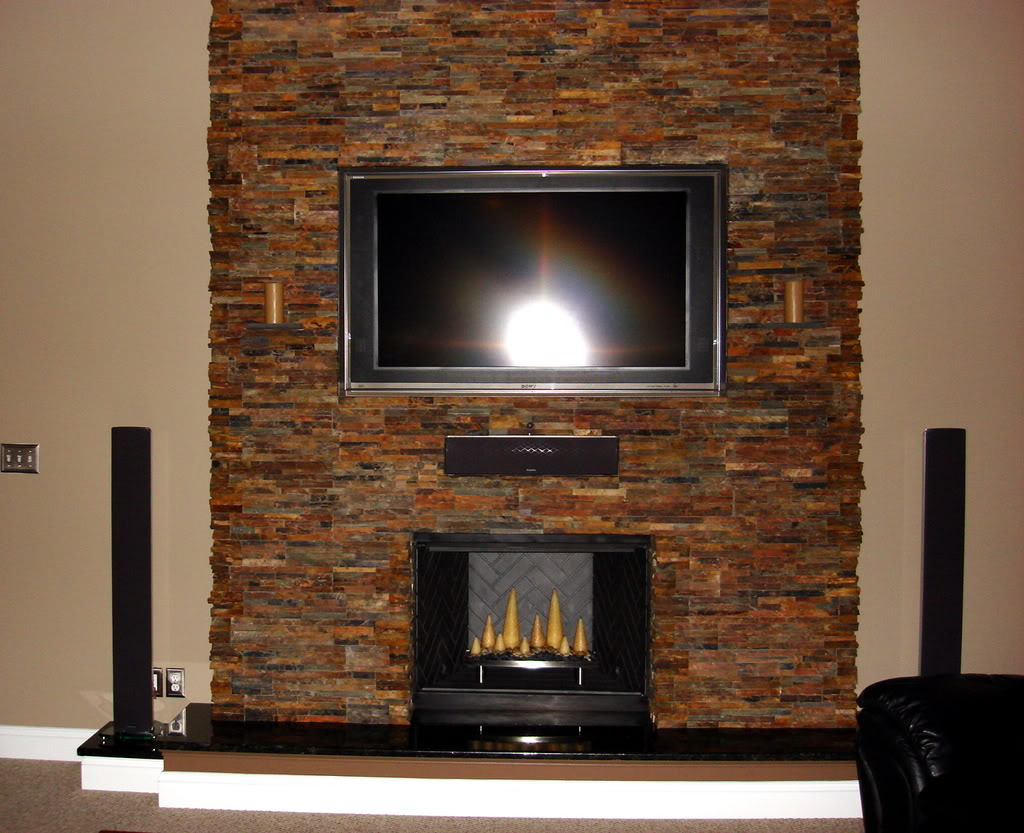 Elegant Design Of The Stone Fireplace Surround With Wall Mounted TV Added With Two Speaker On The Side