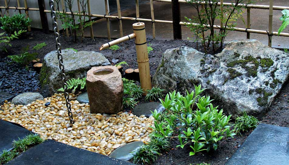 Rustic Bamboo Faucet for Japanese Garden with Nice Gravel and Green Tree