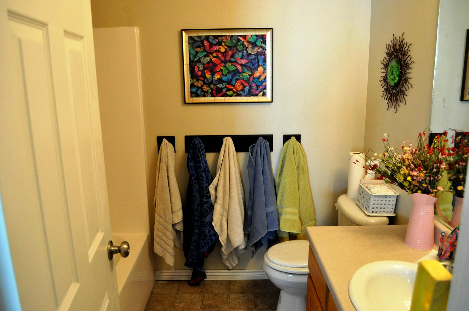 Unique Bathroom With Colorful Painting also Towel Hooks and Toilet