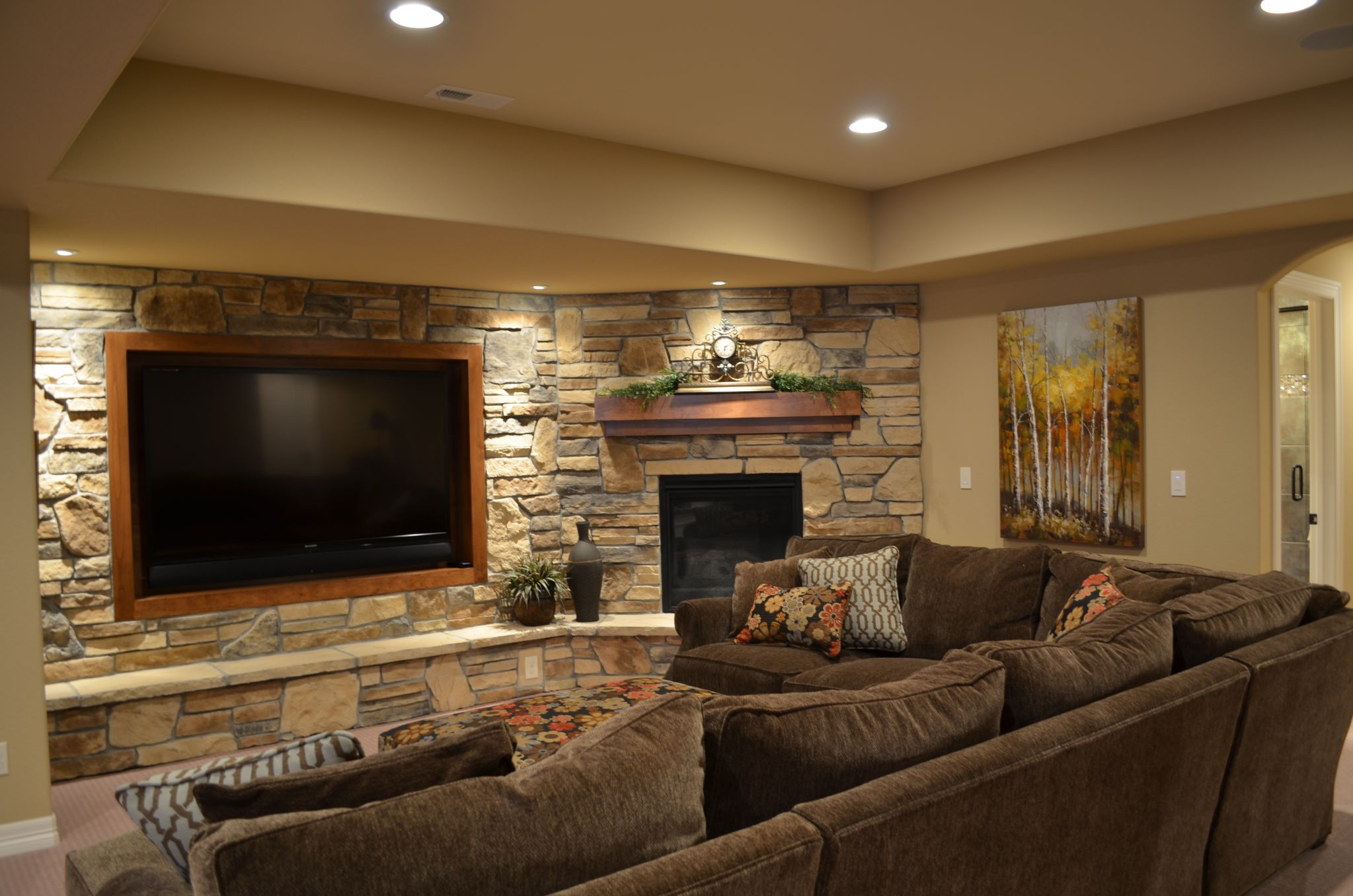 Horrible Basement With Stone Wall Decor also Sectional Sofa Plus Fireplace