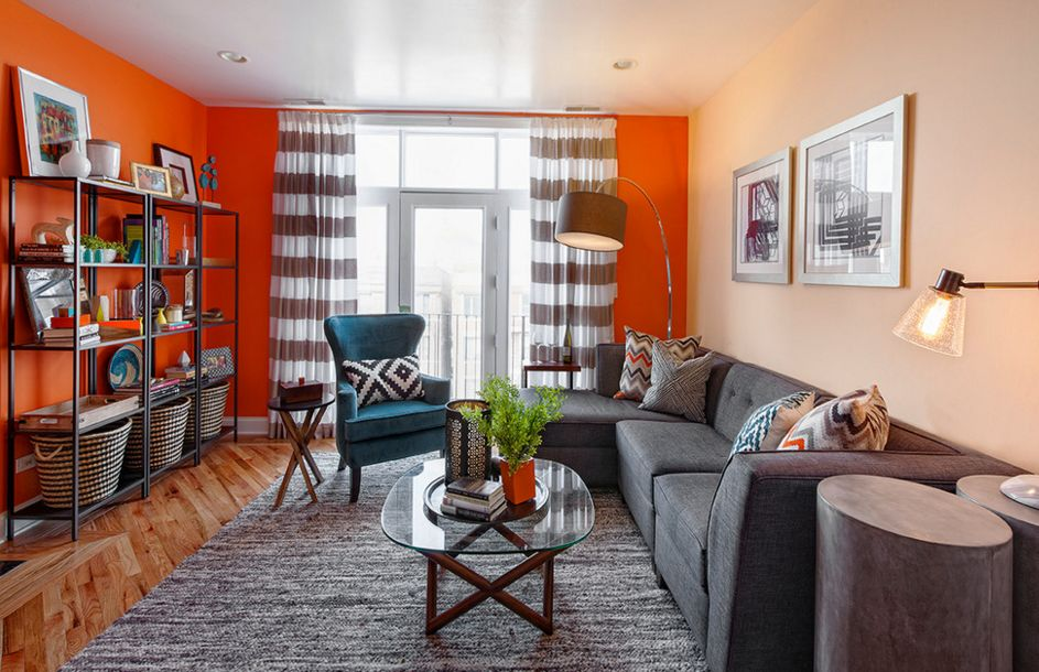 Pleasing Living Space Design Using Gray L Shape Sofa and Orange Wall